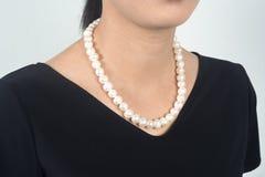 Les femmes asiatiques de portrait ont mis le collier de perle dans des robes noires Image stock