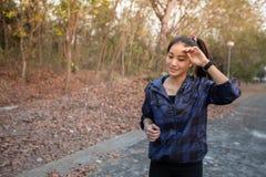 Les femmes asiatiques essuient leur sueur tout en pulsant dehors sur photo stock