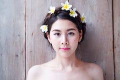 Les femmes asiatiques font face à beau ont des fleurs sur la tête image libre de droits
