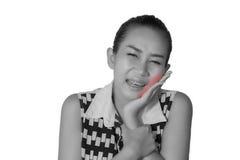 Les femmes asiatiques là sont beaucoup ont un mal de tête et un mal de dents après des orthodonties d'isolement sur le fond blanc Photographie stock