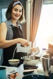 Les femmes asiatiques mélangent les ingrédients d'un gâteau dans une cuvette inoxydable photographie stock