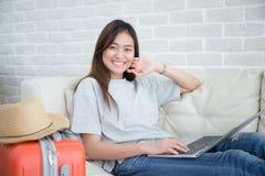 Les femmes asiatiques s'asseyent confortablement sur le sofa et le sourire Utilisez un ordinateur portable pour trouver des infor photographie stock libre de droits
