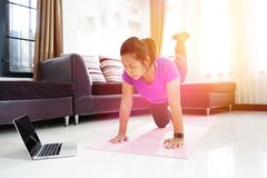 Les femmes asiatiques s'exercent faisant le courbement de retour redressant la jambe vers le haut de la séance d'entraînement à l Photo stock