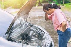 Les femmes asiatiques s'inquiètent et soulignent un problème avec la voiture Photos stock