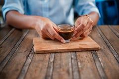 Les femmes asiatiques soulèvent une tasse de café pour boire image libre de droits