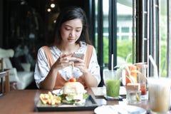 Les femmes asiatiques souriant et heureuses et ont eu plaisir ? manger des hamburgers au caf? et au restaurant sur pour d?tendre  photographie stock libre de droits