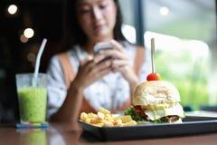 Les femmes asiatiques souriant et heureuses et ont eu plaisir ? manger des hamburgers au caf? et au restaurant sur pour d?tendre  image stock
