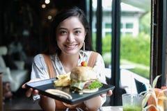 Les femmes asiatiques souriant et heureuses et ont eu plaisir ? manger des hamburgers au caf? et au restaurant sur pour d?tendre  images stock