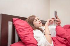 Les femmes asiatiques utilisent le téléphone portable sur le lit dans le matin Femme asiatique dans le lit vérifiant les apps soc images stock
