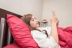 Les femmes asiatiques utilisent le téléphone portable sur le lit dans le matin Femme asiatique dans le lit vérifiant les apps soc photo libre de droits