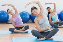 Les femmes avec des yeux ont fermé l'exercice au studio de forme physique images libres de droits