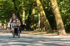 Les femmes avec 2 enfants dans une cargaison font du vélo Photographie stock