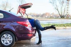 Les femmes avec la tête ont rampé dans le tronc de voiture ouvert Images libres de droits