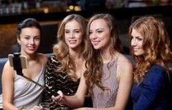 Les femmes avec le selfie de smartphone collent à la boîte de nuit Photos stock