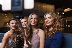 Les femmes avec le selfie de smartphone collent à la boîte de nuit Image libre de droits