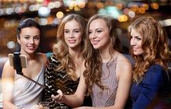 Les femmes avec le selfie de smartphone collent à la boîte de nuit Images stock