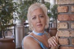 Les femmes blondes mûres se penchent avec des mains sur un mur de briques regardant la caméra avec un sourire agréable photographie stock