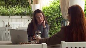 Les femmes caucasiennes attirantes parlent de leurs adventuries pendant la conversation amicale au mouvement lent de café banque de vidéos