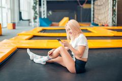 Les femmes caucasiennes jouent avec son téléphone intelligent dans le trempoline photos stock