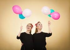 Les femmes comme de petites filles veulent la mouche loin par des ballons Photo libre de droits