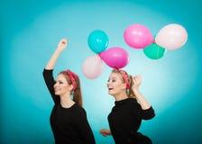 Les femmes comme de petites filles veulent la mouche loin par des ballons Image stock