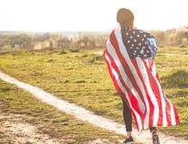 Les femmes courant dans le domaine avec le drapeau am?ricain Etats-Unis c?l?brent le 4?me juillet image stock