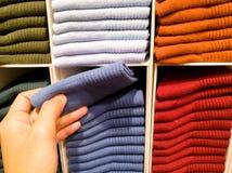 Les femmes cueillent à la main la chaussette bleu-foncé de la pile de chaussettes sur des étagères à vendre dans le magasin d'hab photographie stock