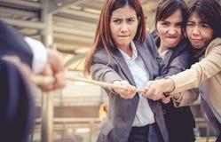 Les femmes d'affaires aident à tirer la corde contre l'homme d'affaires Concentré image stock