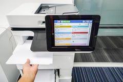 Les femmes d'affaires prennent la feuille de papier imprimée de l'imprimante de bureau Photo libre de droits
