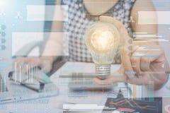Les femmes d'affaires remettent tenir l'ampoule avec le graphique de technologie photographie stock