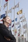 Les femmes d'affaires se tenant avec des bras ont croisé avec des mâts de drapeau à l'arrière-plan. Photo stock