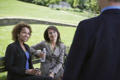 Les femmes d'affaires sur le banc de parc regarde l'homme d'affaires Image libre de droits
