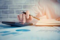 Les femmes d'affaires travaillent avec la calculatrice et l'ordinateur portable, le stylo et le carnet photographie stock