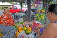 Les femmes d'insulaires de cuisinier commerce avec les billets de banque a du dollar d'Islands de cuisinier Images stock