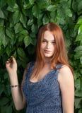 Les femmes d'une chevelure de gingembre posant en vert part dehors Photographie stock libre de droits