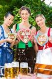 Les femmes dans des vêtements bavarois traditionnels beergarden dedans Photographie stock