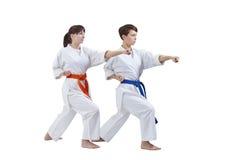 Les femmes dans le karategi forment le bras de poinçon sur un fond blanc Photographie stock