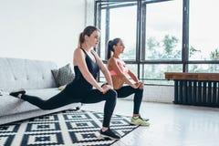 Les femmes de forme physique faisant en avant l'un mouvement brusque avant d'étape de jambe exerce la séance d'entraînement Photos libres de droits