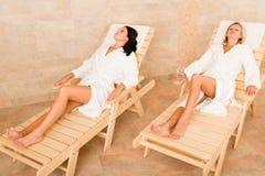 Les femmes de la pièce deux de station thermale de beauté détendent des soleil-bâtis Image stock