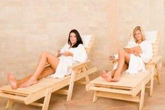 Les femmes de la pièce deux de station thermale de beauté détendent des soleil-bâtis Photographie stock libre de droits