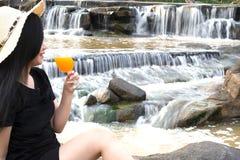 Les femmes de portrait remettent la participation ont fra?chement serr? le jus d'orange en verre avec le fond de cascade photographie stock