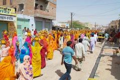 Les femmes de Rajasthani utilisant les sarees jaunes et rouges tenant des noix de coco et des pots participent à un cortège relig photographie stock