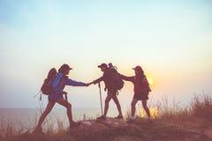 Les femmes de randonneur de travail d'équipe aidant son ami s'élèvent  photographie stock libre de droits