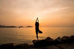 Les femmes de silhouette pratiquent le yoga Photographie stock
