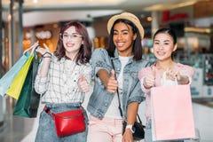 Les femmes de sourire avec des paniers montrant des pouces lèvent des signes au centre commercial Photo libre de droits