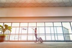 Les femmes de voyageur prévoient et le sac à dos voient l'avion au vitrail d'aéroport, au sac de touristes de prise de fille et à Image stock