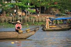 Les femmes dirigent avec des bateaux sur une rivière (Vietnam) Photos stock