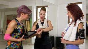 Les femmes donnent des leçons particulières à parler du programme de séance d'entraînement utilisant le PC de comprimé d'ordinate banque de vidéos