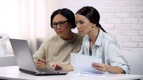 Les femmes emploient la dame adulte de services en ligne étudiant comment payer des utilités sur l'ordinateur portable photos libres de droits