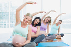 Les femmes enceintes dans le yoga classent se reposer sur des tapis étirant des bras Photographie stock
